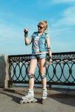Meisje op rollerblades die zich in een zonnig helder licht bevinden Sportlevensstijl Stock Afbeeldingen