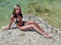 Meisje op rotsachtig strand [1] Stock Foto's