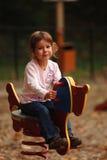 Meisje op speelplaatsstuk speelgoed Stock Fotografie