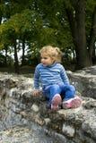 Meisje op steenmuur Stock Foto