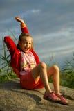 Meisje op stoun dichtbij overzees Stock Foto's