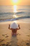 meisje op strand die bij zonsondergang een rijst-hoed 2 dragen stock foto