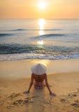 meisje op strand die bij zonsondergang rijsthoed 3 dragen stock fotografie
