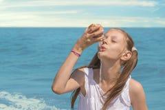 Meisje op strand het spelen met een zeeschelp royalty-vrije stock fotografie