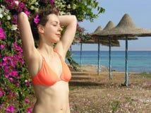 Meisje op strand met bloemen stock foto