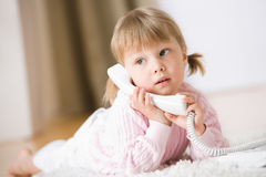 Meisje op tapijt met telefoon het roepen Stock Fotografie