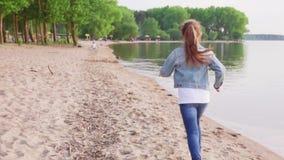 Meisje op zandig strand langs kustlijn bij de zomerdag die in werking wordt gesteld stock videobeelden