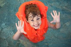 Meisje in opblaasbaar vest in pool stock foto
