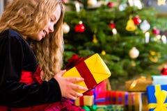 Meisje openen huidig op Kerstmisdag Royalty-vrije Stock Afbeeldingen