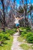 Meisje in openlucht het springen over boom gevallen over spoor royalty-vrije stock afbeelding