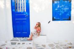 Meisje in openlucht in oude straten een Mykonos Jong geitje bij straat van typisch Grieks traditioneel dorp met witte muren en royalty-vrije stock fotografie