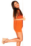 Meisje in oranje kleding achter witte muur stock afbeelding