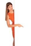 Meisje in oranje kleding achter witte raad stock afbeelding