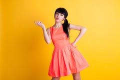 Meisje in oranje kleding op handen gele als achtergrond omhoog royalty-vrije stock afbeeldingen