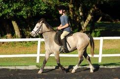 Meisje in paardrijdenles Stock Foto's