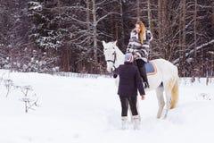 Meisje, paardtrainer en wit paard in de winter Stock Fotografie