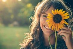 Meisje in park die gezicht behandelen met zonnebloem Stock Afbeelding