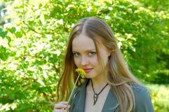 Meisje in park met geheimzinnige glimlach en paardebloem Stock Fotografie