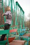 Meisje in park op oude schommeling Stock Afbeeldingen