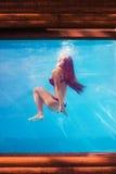Meisje in pool onderwater door het glas stock foto