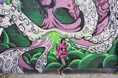 Meisje posoes voor het groot werk van de graffitikunst, Peking, China Stock Foto