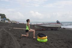 Meisje, powerboat en gele, groene Drijvende Ring op strand, bewolking, wolken, golven stock afbeeldingen