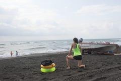 Meisje, powerboat en gele, groene Drijvende Ring op strand, bewolking, wolken, golven royalty-vrije stock fotografie