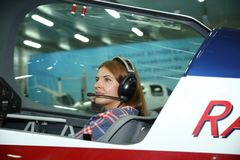 Meisje proef in hoofdtelefoons in een sportenvliegtuig die klaar voor vlucht worden stock foto's