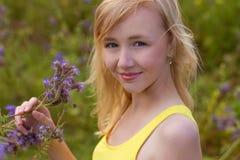 Meisje in purpere bloemen in openlucht in de zomer Stock Afbeelding