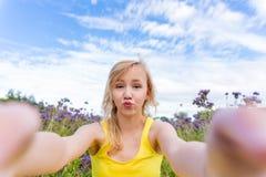 Meisje in purpere bloemen in openlucht in de zomer Stock Foto's