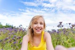 Meisje in purpere bloemen in openlucht in de zomer Stock Afbeeldingen
