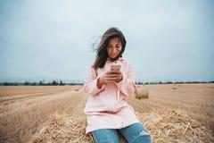 Meisje in regenjas Het meisje van het de herfstportret hipster in een laag Vrouw die Telefoon met behulp van Royalty-vrije Stock Afbeeldingen