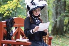 Meisje in retro kleding voorbij eeuw gelezen brief op de bank Royalty-vrije Stock Fotografie