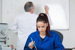 Meisje in roboticaklasse het solderen met leraar op achtergrond Stock Fotografie