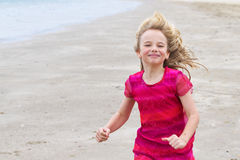 Meisje in rode kleding die op het strand loopt Stock Afbeeldingen