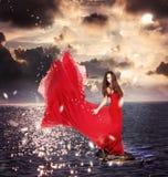 Meisje in Rode Kleding die zich op OceaanRotsen bevindt Royalty-vrije Stock Foto