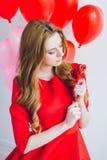 Meisje in rode kleding met ballons in de vorm van een hart Royalty-vrije Stock Afbeeldingen