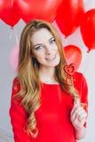 Meisje in rode kleding met ballons in de vorm van een hart Stock Afbeeldingen