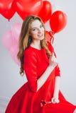 Meisje in rode kleding met ballons in de vorm van een hart Stock Foto's
