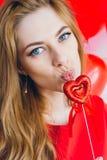 Meisje in rode kleding met ballons in de vorm van een hart Stock Fotografie