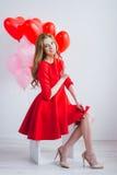 Meisje in rode kleding met ballons in de vorm van een hart Stock Afbeelding