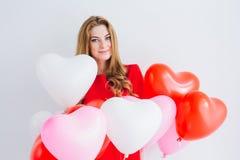 Meisje in rode kleding met ballons in de vorm van een hart Stock Foto