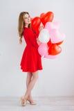 Meisje in rode kleding met ballons in de vorm van een hart Royalty-vrije Stock Foto