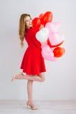 Meisje in rode kleding met ballons in de vorm van een hart Royalty-vrije Stock Foto's