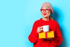 Meisje in rode sweater met giftdoos en kop van koffie royalty-vrije stock afbeelding