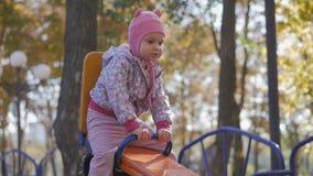 Meisje in roze hoed op schommeling in het park van de de herfststad stock videobeelden