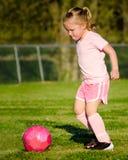Meisje in roze speelvoetbal op gebied Stock Fotografie