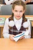 Meisje in school eenvormig het doen thuiswerk op het patroon op de stof stock foto's
