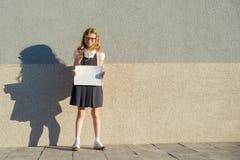 Meisje in school eenvormig met rugzak die een lege witte bladaffiche tonen stock foto