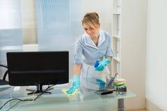 Meisje schoonmakend bureau met veerstofdoek stock fotografie